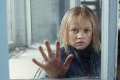Deprimiertes poot Mädchen, das nahes Fenster steht Lizenzfreies Stockbild