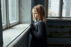 Deprimiertes poot Mädchen, das nahes Fenster steht Stockfoto