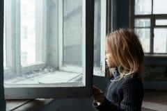Deprimiertes poot Mädchen, das nahes Fenster steht Lizenzfreies Stockfoto