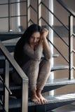 Deprimiertes Sitzen der jungen Frau Stockbild