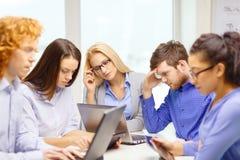 Deprimiertes Team mit Laptop- und Tabellen-PC-Computern Stockbilder