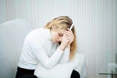 Deprimiertes und trauriges a des positiven des Schwangerschaftstests Gefühls der jungen Frau stockfoto