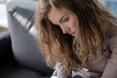 Deprimiertes weibliches Sitzen auf gemütlichem Sofa Lizenzfreie Stockfotografie