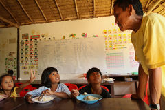 Deprived children in the classroom at lunch time. Unknown children in the classroom at lunch time at school by project Cambodian Kids Care to help deprived Stock Images