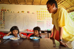 Deprived children in the classroom at lunch time. Unknown children in the classroom at lunch time at school by project Cambodian Kids Care to help deprived Stock Photography