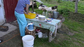 Deprived woman wash dirty dishes and cats walk. rural poverty stock video footage