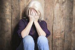 Deprymuje starszej osoby z drewnianym tłem fotografia stock