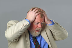 In dept. Businessman not satisfied with monthly payment on grey background Royalty Free Stock Photo