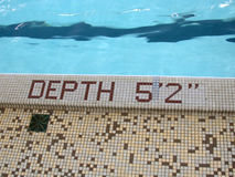 Depth: 5 foot 2, pool of blue... Side of pool, with depth marker inset with tiles to state Depth 5 foot 2 inches stock image