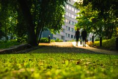 Grassy path and silhouettes of people. Depth of field low to the ground while silhouettes of people traverse a grassy path walkway in Turku, Finland Royalty Free Stock Photo