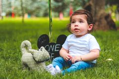 Depth of Field Photography of Baby Sitting on Green Grass stock photography