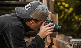 Depth of Field Photography of Man Holding Dslr Camera Stock Image