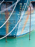 Depth scale on bow of anchored ship in grungy blue. Closeup of the bow hull with floatation depth scale gauge of a ship with grungy rust streaks from corroded royalty free stock photos