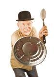 Der Ältere, der mit Löffel und kann Kappe sich verteidigt Lizenzfreie Stockfotografie