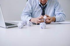 Der ältere Geschäftsmann, der deprimiert und an seinem Schreibtisch frustriert wird mit Problemen mit einem Stapel der Arbeit ers stockbilder