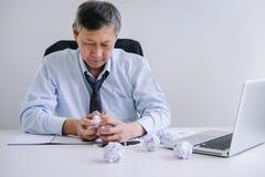 Der ältere Geschäftsmann, der deprimiert und an seinem Schreibtisch frustriert wird mit Problemen mit einem Stapel der Arbeit ers stockfotos