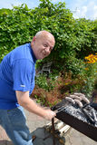 Der ältere Mann bereitet Würste ein Grill auf einem Messingarbeiter zu Stockfotos