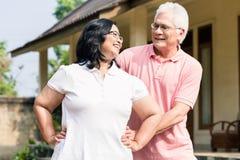 Der ältere Mann, der seine Frau während des Aufwärmens unterstützt, übt outdoo aus Lizenzfreies Stockfoto