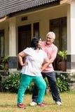 Der ältere Mann, der seine Frau während des Aufwärmens unterstützt, übt outdoo aus Stockfotografie