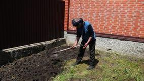 Der ältere Mann gräbt eine Schaufel der Boden nahe einem hohen Zaun im sonnigen Wetter stock video footage