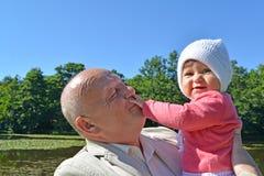 Der ältere Mann hält auf Händen die kleine Enkelin im Park Lizenzfreies Stockfoto