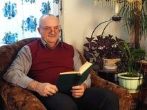 Der ältere Mann mit einem Buch in einem Stuhl Lizenzfreie Stockfotos