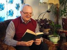 Der ältere Mann mit einem Buch in einem Stuhl Lizenzfreie Stockbilder