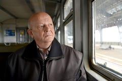 Der ältere Mann schaut durchdacht aus dem Gewinn des elektrischen Zugs heraus Stockfotos