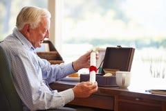 Der ältere setzende Mann wird in Kasten Lizenzfreie Stockbilder