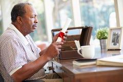 Der ältere setzende Mann wird in Kasten Lizenzfreies Stockbild