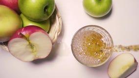 Der Äpfel Saft auf dem Tisch und der Zeitlupe gießt aus oben stock footage