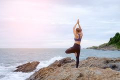Der übende Yogasonnenuntergang der Frau auf dem Strand lizenzfreies stockfoto