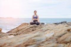 Der übende Yogasonnenuntergang der Frau auf dem Strand stockbilder