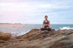 Der übende Yogasonnenuntergang der Frau auf dem Strand stockfotos