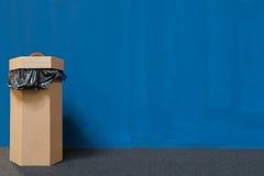 Der überschüssige Behälter oder Abfalleimer, die vom Recyclingpapier, Blau gemalter Wandhintergrund mit Kopienraum hergestellt we Stockfotografie
