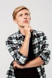 Der überzeugte denkende blonde hübsche junge Mann, der zufälliges kariertes Hemd mit den Händen trägt, kreuzte auf dem Kasten, de Stockfotos