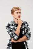 Der überzeugte denkende blonde hübsche junge Mann, der zufälliges kariertes Hemd mit den Händen trägt, kreuzte auf dem Kasten, de Stockbilder