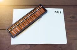 Der Abakus wurde auf ein Buch gesetzt, um im Jahre 2018 zu schreiben Stockfotografie