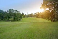 Der Abendgolfplatz hat das Sonnenlicht, das unten am Golfplatz glänzt stockbilder