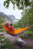 Der Abenteurer, der in der Hängematte in den Bergen sich entspannt, macht ein Foto u Lizenzfreies Stockfoto