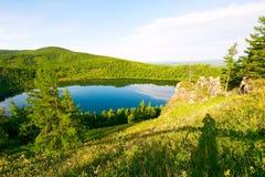 Der Abhang und der blaue See Stockbilder
