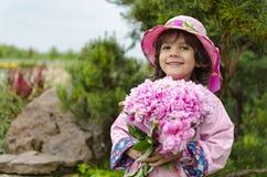 Der Abschluss des kleinen Mädchens in einem rosa Hut und in einem Regenmantel Lizenzfreie Stockfotos