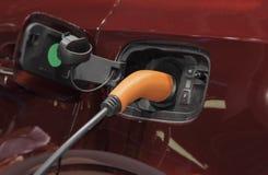 Der Abschluss oben des eklektischen Ladegerätsteckers, der SUV-Auto auflädt Stockfotos