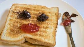 Der Abschluss oben des geschmackvollen Brottoasts und der Erdbeermarmelade mit Schokoladenverbreitung Lizenzfreie Stockfotos