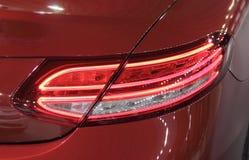 Der Abschluss oben des hinteren Bremslichts des roten luxuriösen Autos Stockfoto