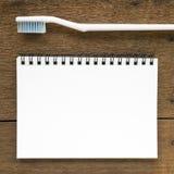 Der Abschluss oben des leeren weißen Notizbuches und der weißen Zahnbürste Stockfotografie