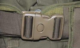 Der Abschluss oben der militärischen grünen Plastikgürtelschnalle Stockfotos