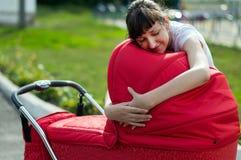 Der Abschluss oben - Mutter freut sich das neugeborene Kind im Wagen Lizenzfreie Stockbilder