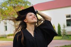 Der Absolvent im Umhang schaut oben Stockbilder