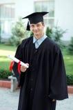 Der Absolvent mit einem Diplom in der Hand Lizenzfreies Stockfoto